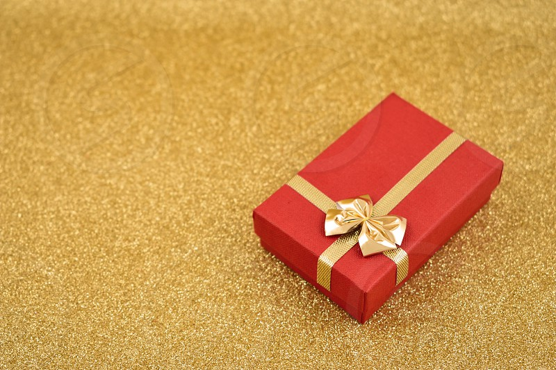 Red gift box with golden bow. Red gift box on a golden background. Golden holiday background with gift. Golden festive background with copy space for text photo